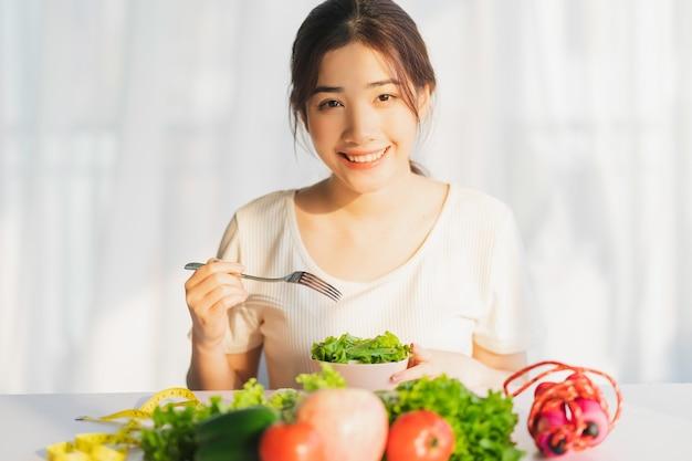 La giovane donna sta mangiando verdure verdi per perdita di peso