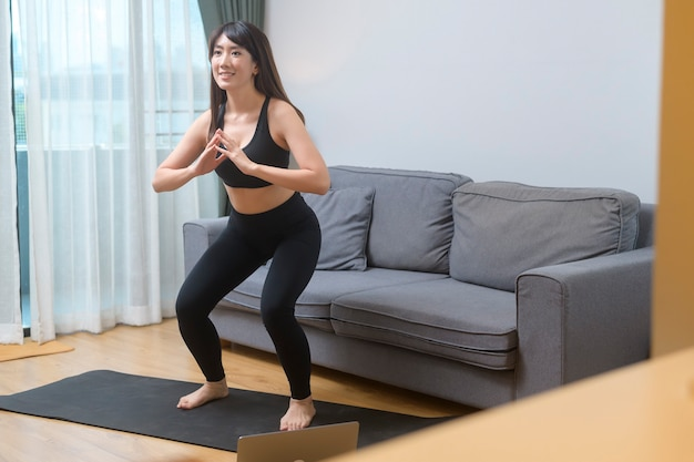 Una giovane donna si sta esercitando e guarda la lezione di fitness di formazione online sul computer portatile nel soggiorno di casa, lo sport, il fitness e il concetto di tecnologia.