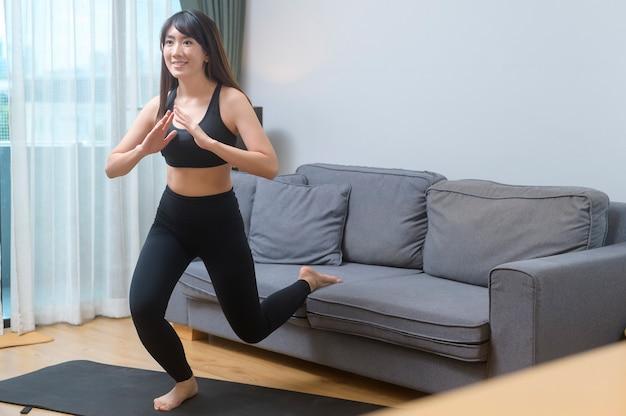 Una giovane donna si sta esercitando e guarda la lezione di fitness di formazione online sul computer portatile in salotto a casa, sport, fitness e concetto di tecnologia.