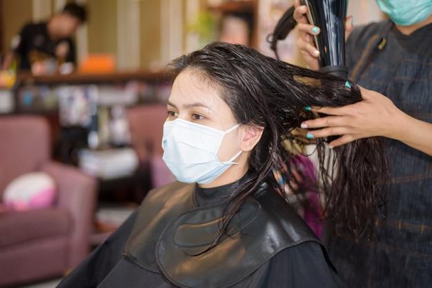 Una giovane donna sta ottenendo un taglio di capelli in un parrucchiere, indossando la maschera per la protezione covid-19, concetto di sicurezza del salone