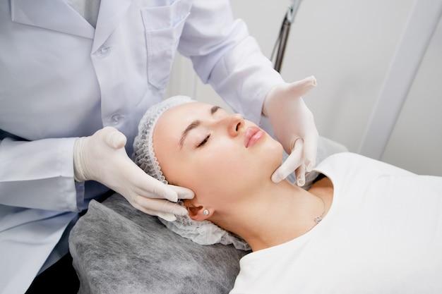 La giovane donna sta preparando la sua pelle con un massaggio per renderla pronta e rilassata per la procedura presso il salone di bellezza.