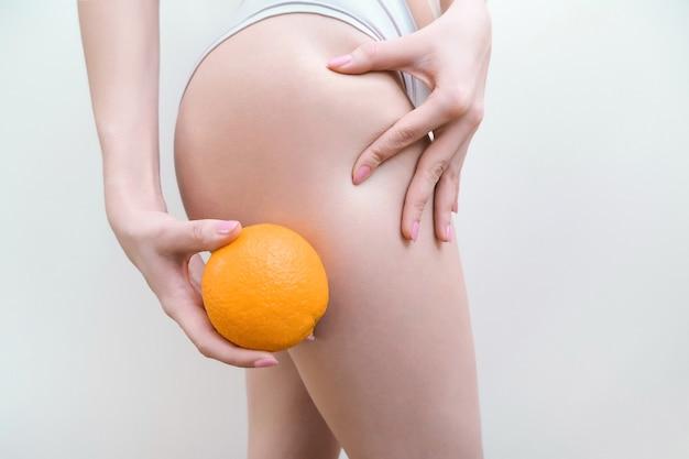 La giovane donna sta tenendo un'arancia su uno sfondo chiaro. concetto di problema di cellulite