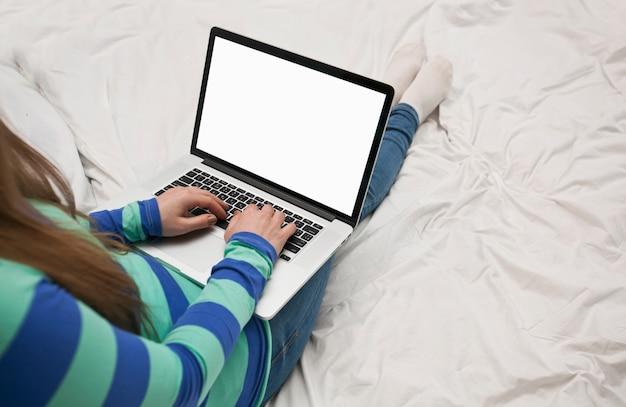 Giovane donna è sdraiata sul letto con un computer portatile