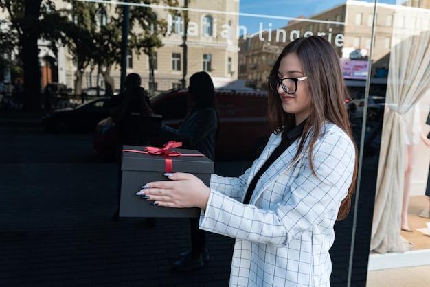 La giovane donna sta tenendo ordinatamente la scatola nera con l'arco rosso. ritratto di ragazza alla moda con confezione regalo nelle sue mani.