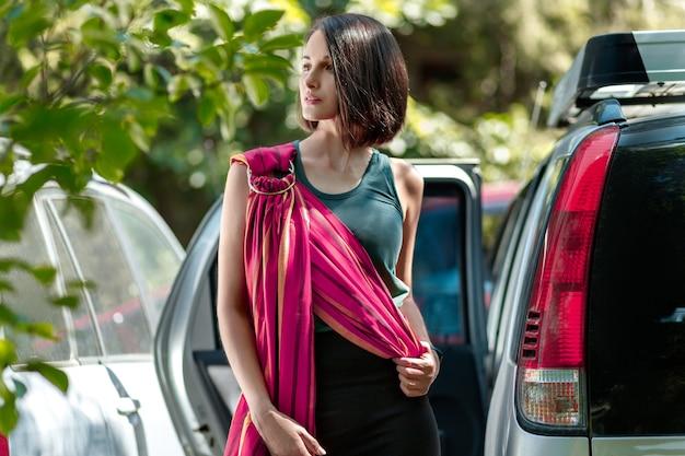 La giovane donna sta preparando un'imbracatura ad anello per portare il bambino fuori dall'auto babywearing e mani libere