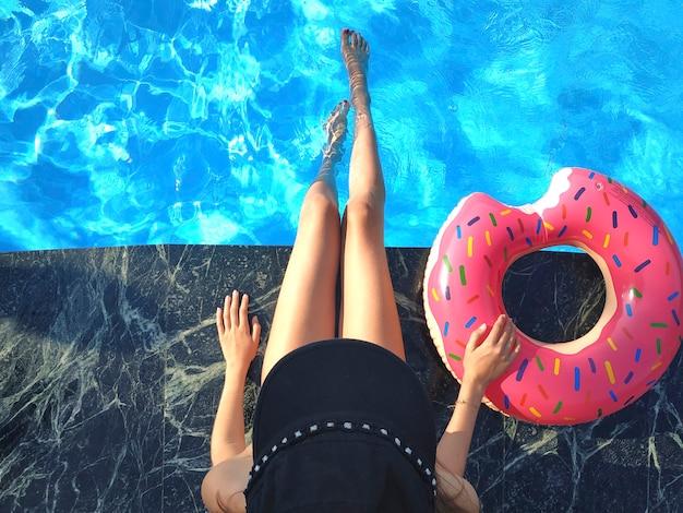 La giovane donna si sta rilassando con la ciambella nella piscina del resort termale. vista dall'alto. rilassante, vacanza, vacanza estiva concetto idilliaco.