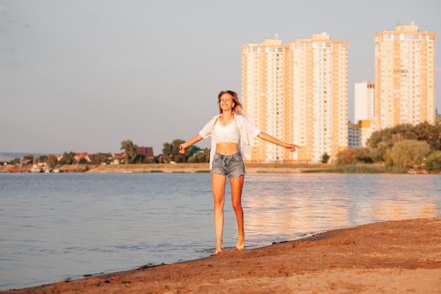 Una giovane donna gira sullo sfondo di un paesaggio urbano, una bella bionda felice in un...