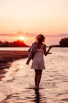 Una giovane donna sta girando sullo sfondo del tramonto una bella giovane bionda in un s...