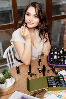 Una giovane donna sta testando gli aromi degli oli naturali. una bella mora si siede a un tavolo di legno e si gode il suo lavoro.