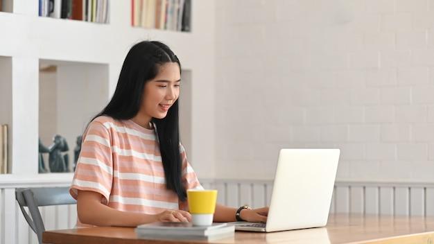 La giovane donna sta scrivendo su un computer portatile mentre era seduto alla scrivania in legno.