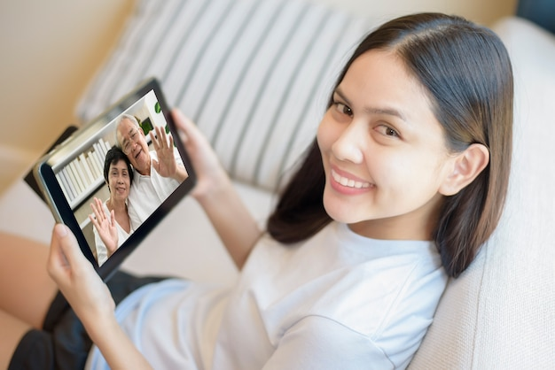 Una giovane donna sta utilizzando tablet per videochiamate o webcam per nonni, tecnologia delle telecomunicazioni, concetto di famiglia genitoriale.