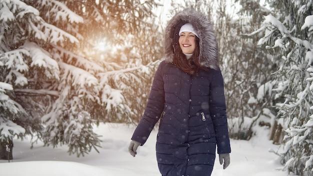 La giovane donna sta camminando lungo una bellissima foresta invernale, la luce del sole