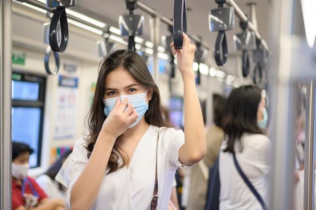 Una giovane donna indossa una maschera protettiva in metropolitana, protezione covid-19, viaggi sicuri, nuova normalità, allontanamento sociale, trasporto sicuro, viaggio sotto il concetto di pandemia.