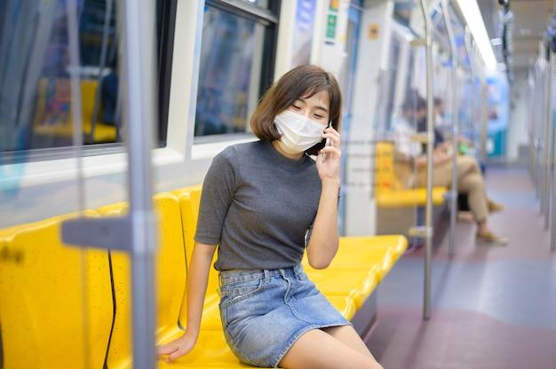 Una giovane donna indossa una maschera protettiva in metropolitana, protezione covid-19, viaggi sicuri, nuova normalità, allontanamento sociale, trasporto sicuro, viaggi sotto il concetto di pandemia.