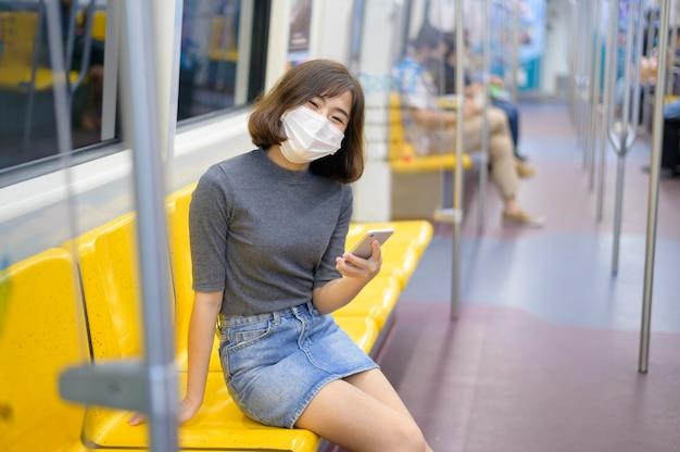 Una giovane donna indossa una maschera protettiva in metropolitana, protezione covid-19, viaggio sicuro, nuova normalità, allontanamento sociale, trasporto sicuro, viaggio sotto il concetto di pandemia.
