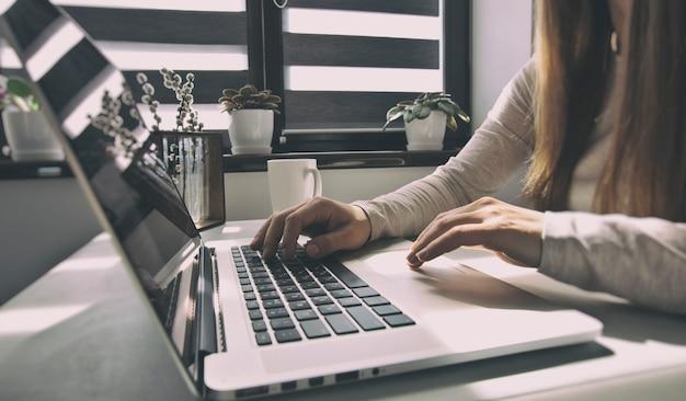 La giovane donna sta lavorando al laptop a casa sua