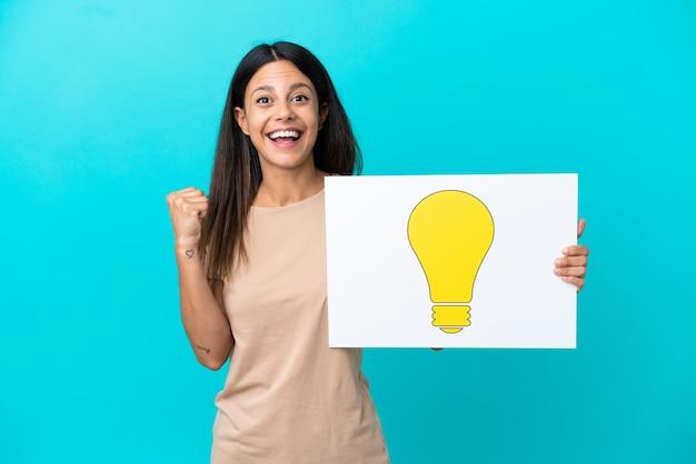 Giovane donna su sfondo isolato tenendo un cartello con l'icona della lampadina e celebrando una vittoria