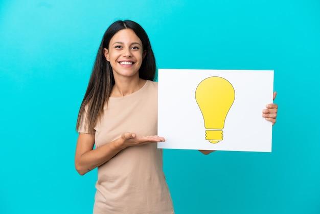 Giovane donna su sfondo isolato tenendo un cartello con l'icona della lampadina e indicandolo