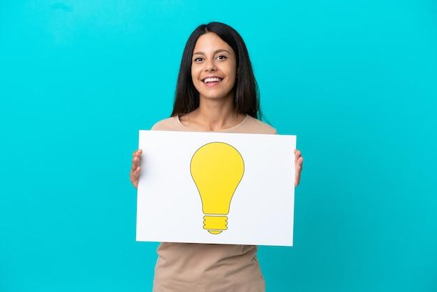 Giovane donna su sfondo isolato che tiene un cartello con l'icona della lampadina con espressione felice