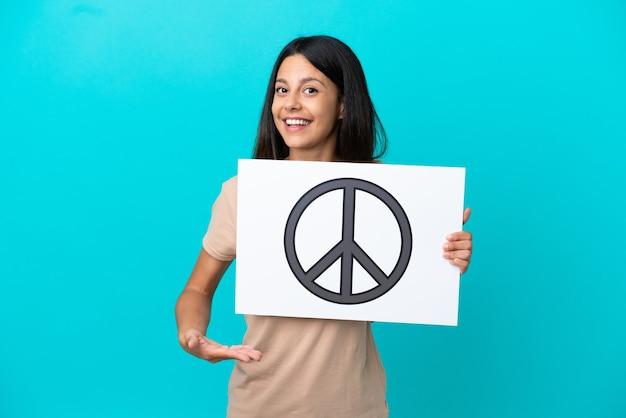 Giovane donna su sfondo isolato tenendo un cartello con il simbolo della pace e indicandolo
