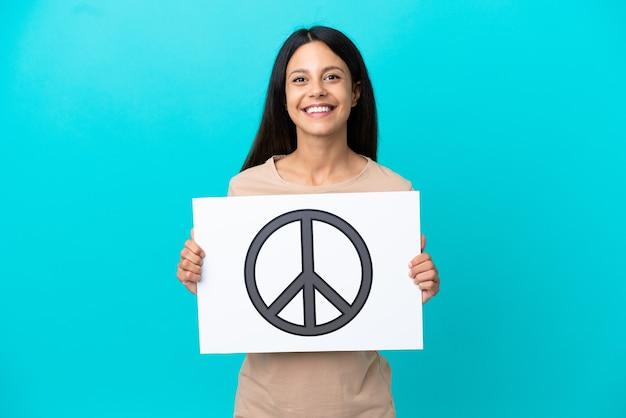 Giovane donna su sfondo isolato che tiene un cartello con il simbolo della pace con espressione felice