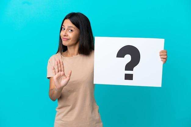 Giovane donna su sfondo isolato tenendo un cartello con il simbolo del punto interrogativo e facendo il segnale di stop