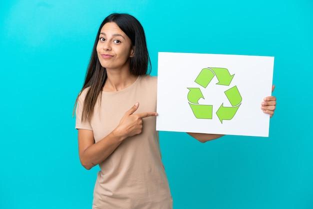 Giovane donna su sfondo isolato tenendo un cartello con l'icona di riciclo e puntandolo