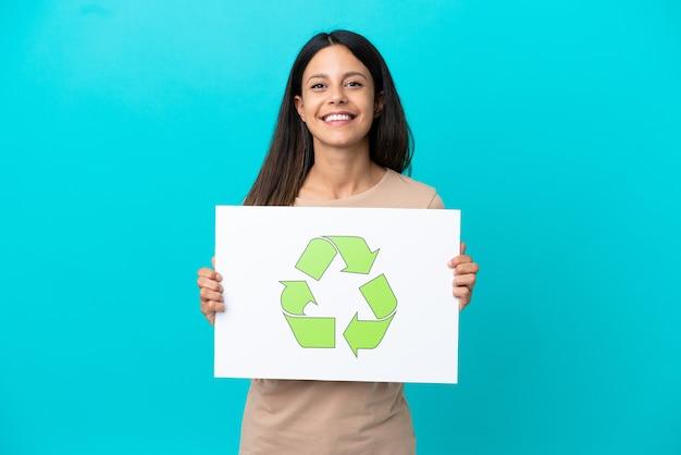 Giovane donna su sfondo isolato in possesso di un cartello con icona di riciclo con espressione felice