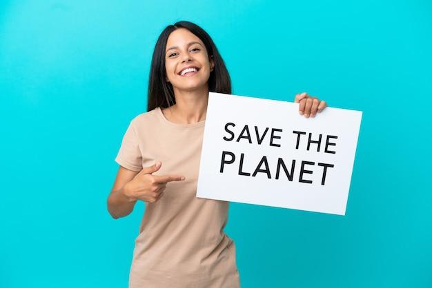 Giovane donna su sfondo isolato tenendo un cartello con il testo salva il pianeta e indicandolo