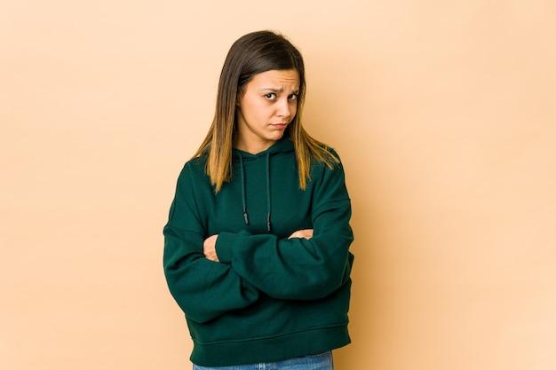 Giovane donna isolata su sfondo beige infelice guardando a porte chiuse con espressione sarcastica.