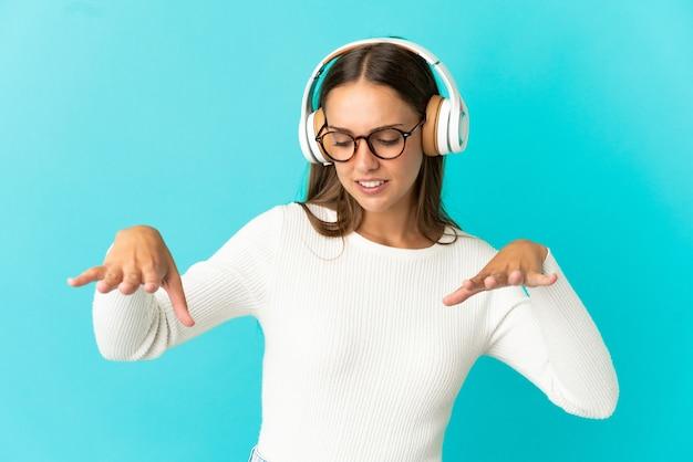 Giovane donna su sfondo blu isolato ascoltando musica e ballando
