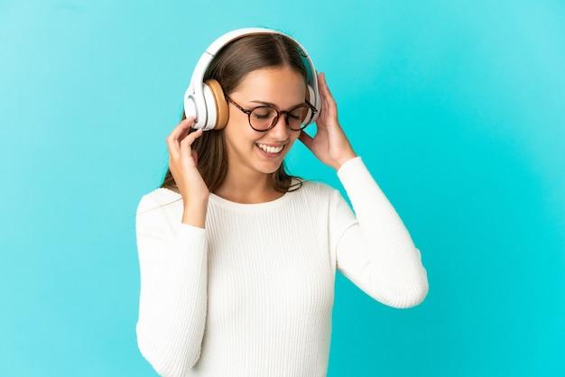 Giovane donna su sfondo blu isolato ascoltando musica e cantando