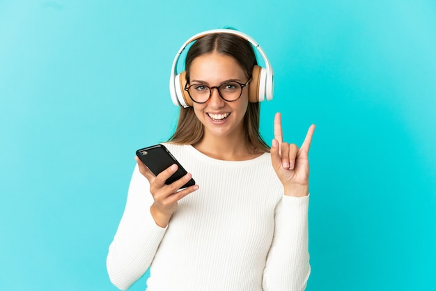 Giovane donna su sfondo blu isolato ascoltando musica con un cellulare che fa gesto rock