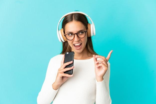 Giovane donna su sfondo blu isolato ascoltando musica con un cellulare e cantando
