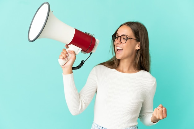 Giovane donna su sfondo blu isolato che grida tramite un megafono per annunciare qualcosa in posizione laterale
