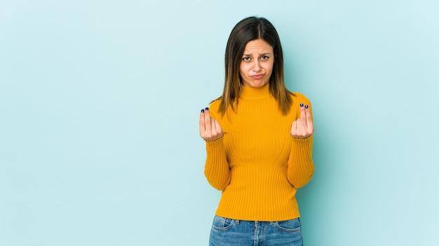 Giovane donna isolata su sfondo blu che mostra che non ha soldi.