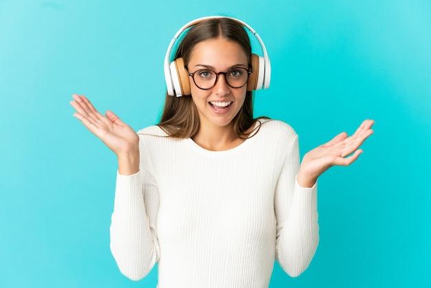 Giovane donna su sfondo blu isolato sorpreso e ascoltando musica