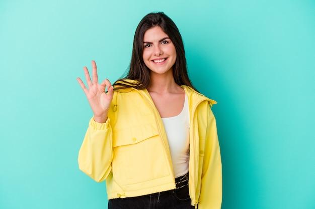 Giovane donna isolata sul muro blu allegro e fiducioso che mostra gesto giusto