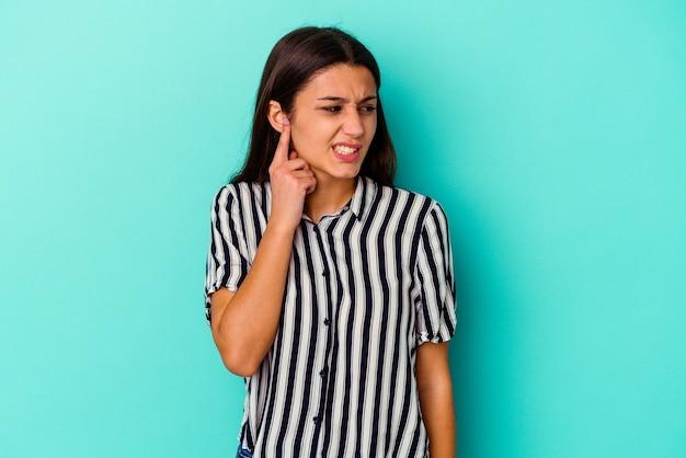 Giovane donna isolata sul muro blu che copre le orecchie con le mani