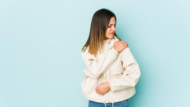 Giovane donna isolata sulla parete blu che ha un dolore alla spalla