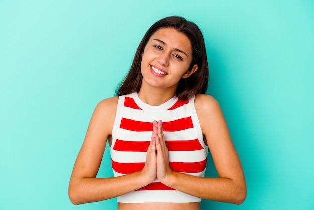 La giovane donna isolata sulla parete blu che tiene le mani nella preghiera vicino alla bocca, si sente sicura