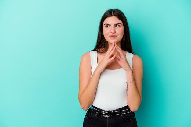Giovane donna isolata sulla parete blu che compongono il piano in mente, creando un'idea