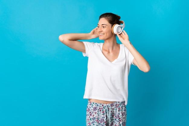 Giovane donna isolata sulla parete blu in pigiama e tenendo un cuscino e ascoltando musica