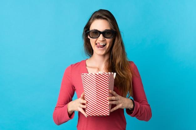 Giovane donna isolata sulla parete blu con gli occhiali 3d e che tiene un grande secchio di popcorn