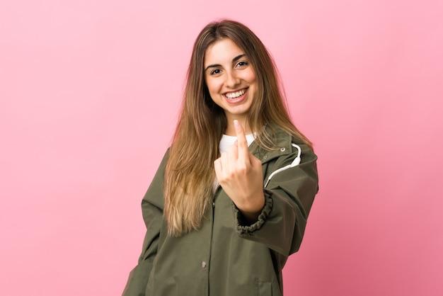Giovane donna sopra la parete rosa isolata che fa gesto venente