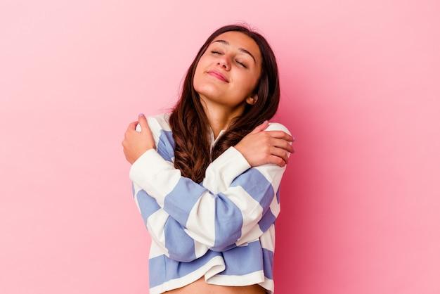 Giovane donna isolata sul muro rosa abbracci, sorridendo spensierata e felice