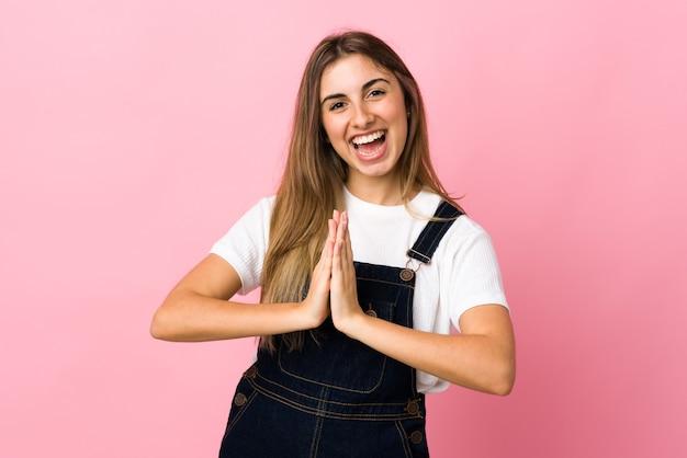 La giovane donna sopra la parete rosa isolata tiene insieme la palma. la persona chiede qualcosa