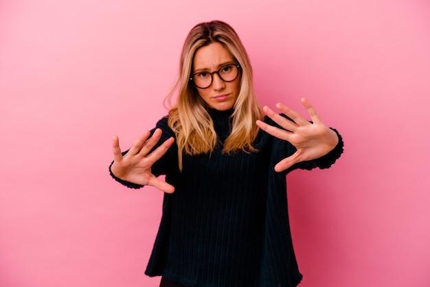 Giovane donna isolata sulla parete rosa che rifiuta qualcuno che mostra un gesto di disgusto