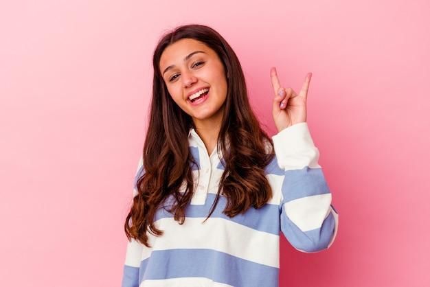Giovane donna isolata sulla parete rosa che mostra un gesto di corna come un concetto di rivoluzione