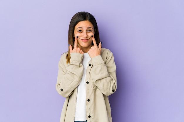 Giovane donna isolata su sfondo viola dubitando tra due opzioni.